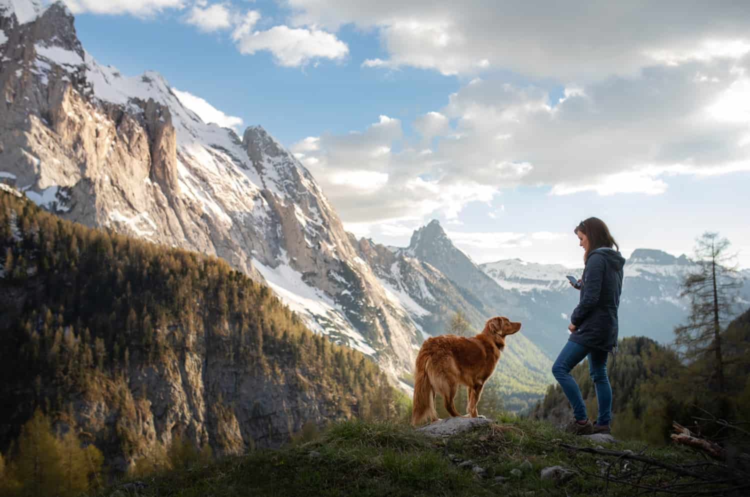 Woman with a dog in the mountains. Autumn mood. Traveling with a pet. Nova Scotia Duck Tolling Retriever
