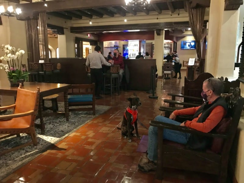 Man and dog sitting in the lobby at La Fonda on the Plaza in Santa Fe, NM