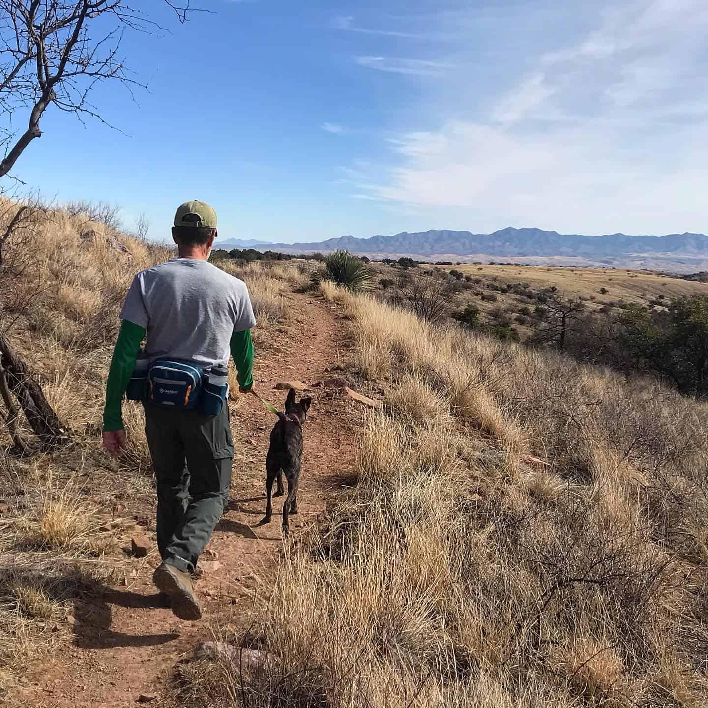 Man and dog hiking on a trail in Arizona