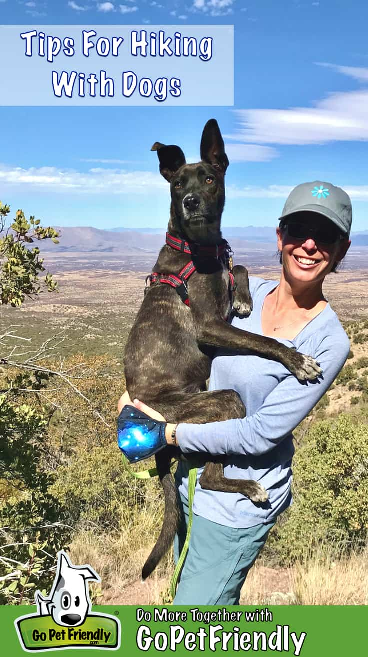 Woman holding dog on a pet friendly hiking trail with mountains in the background