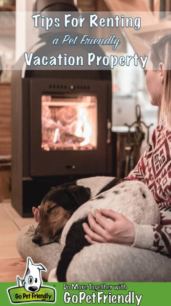 Woman sitting on the floor in a vacation property holding a sleeping dog on her lap while gazing into a glowing fireplace