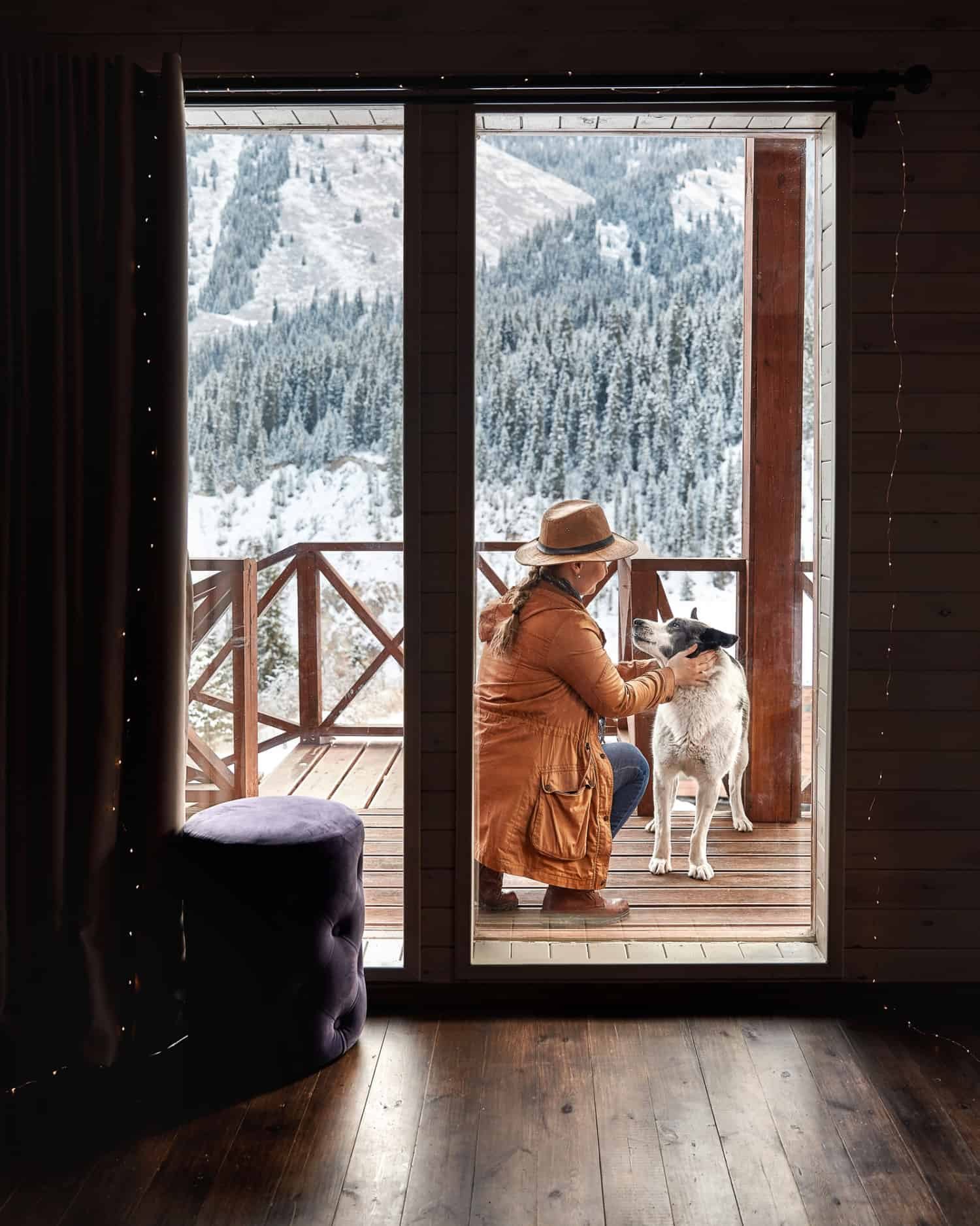 Woman in hat is playing with her dog on the deck of a pet friendly vacation property in the winter