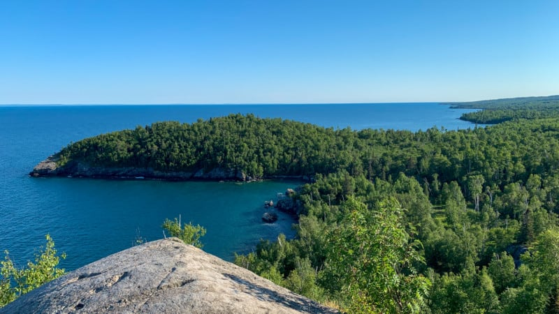 View from a large rock on a hill looking out toward a wooded peninsula in Lake Superior at Split Rock Lighthouse State Park in Minnesota