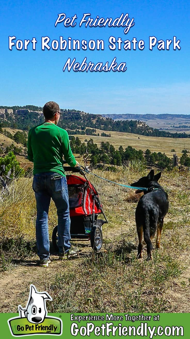 Man pushing a stroller and walking a black dog on a pet friendly trail in Fort Robinson State Park in Nebraska