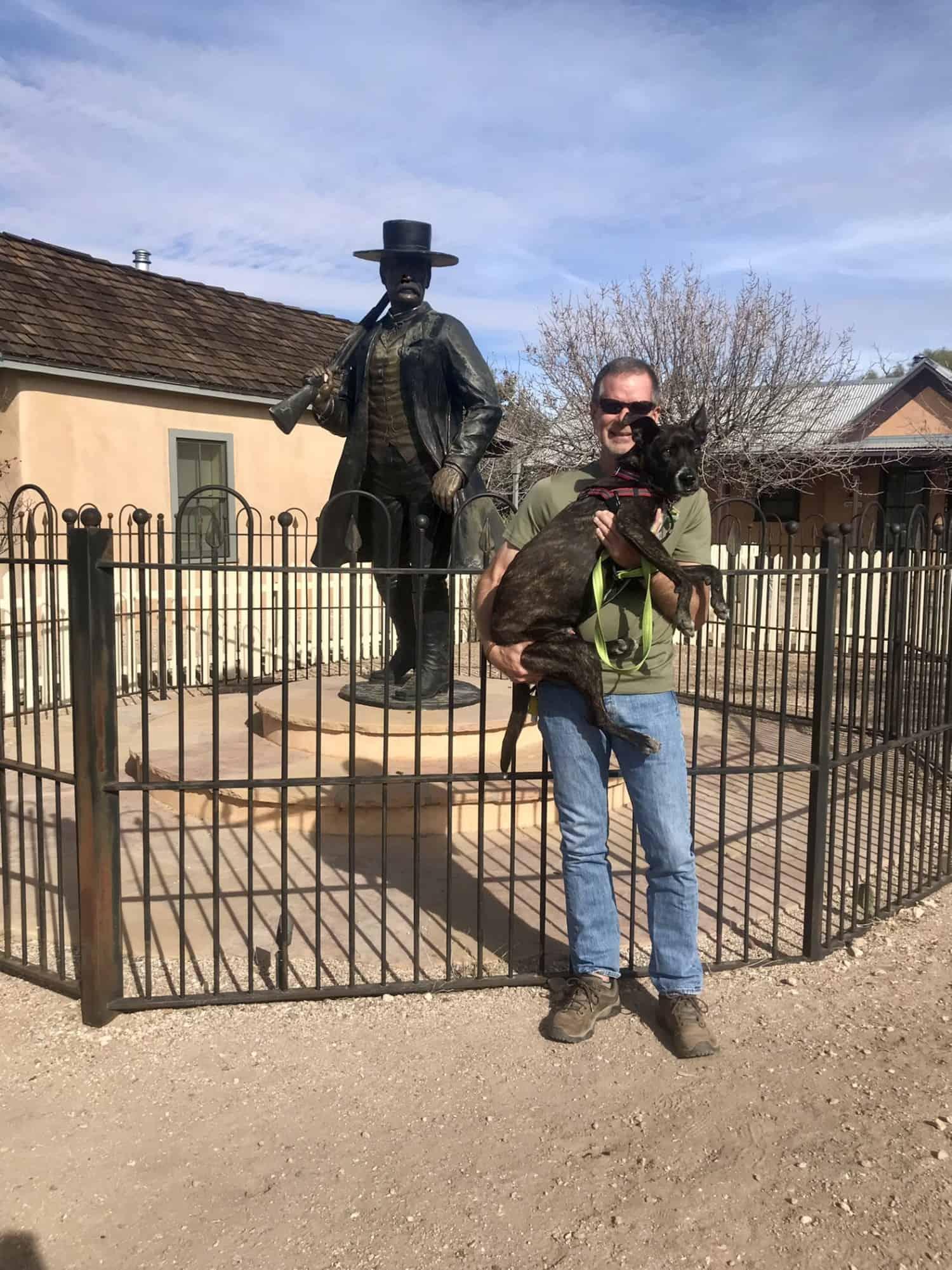 Man holding dog beside statue of Wyatt Earp in Tombstone, AZ