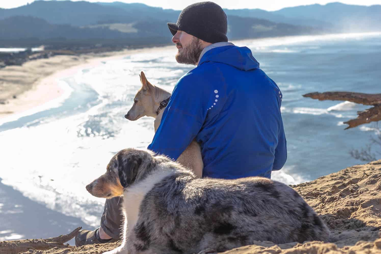 Man in a hat with two dogs enjoying the ocean view along the pet friendly Oregon Coast