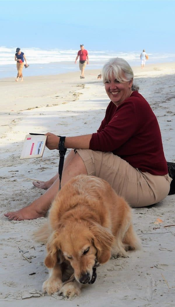 Honey the golden retriever and Pam wait on the beach at Fort Matanzas.