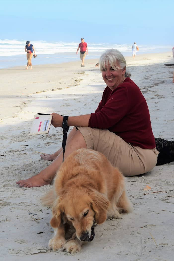 Honey the golden retriever and Pam wait on the beach at Fort Matanzas. | GoPetFriendly.com