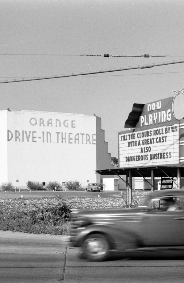 Old car driving by Orange Drive-In movie .