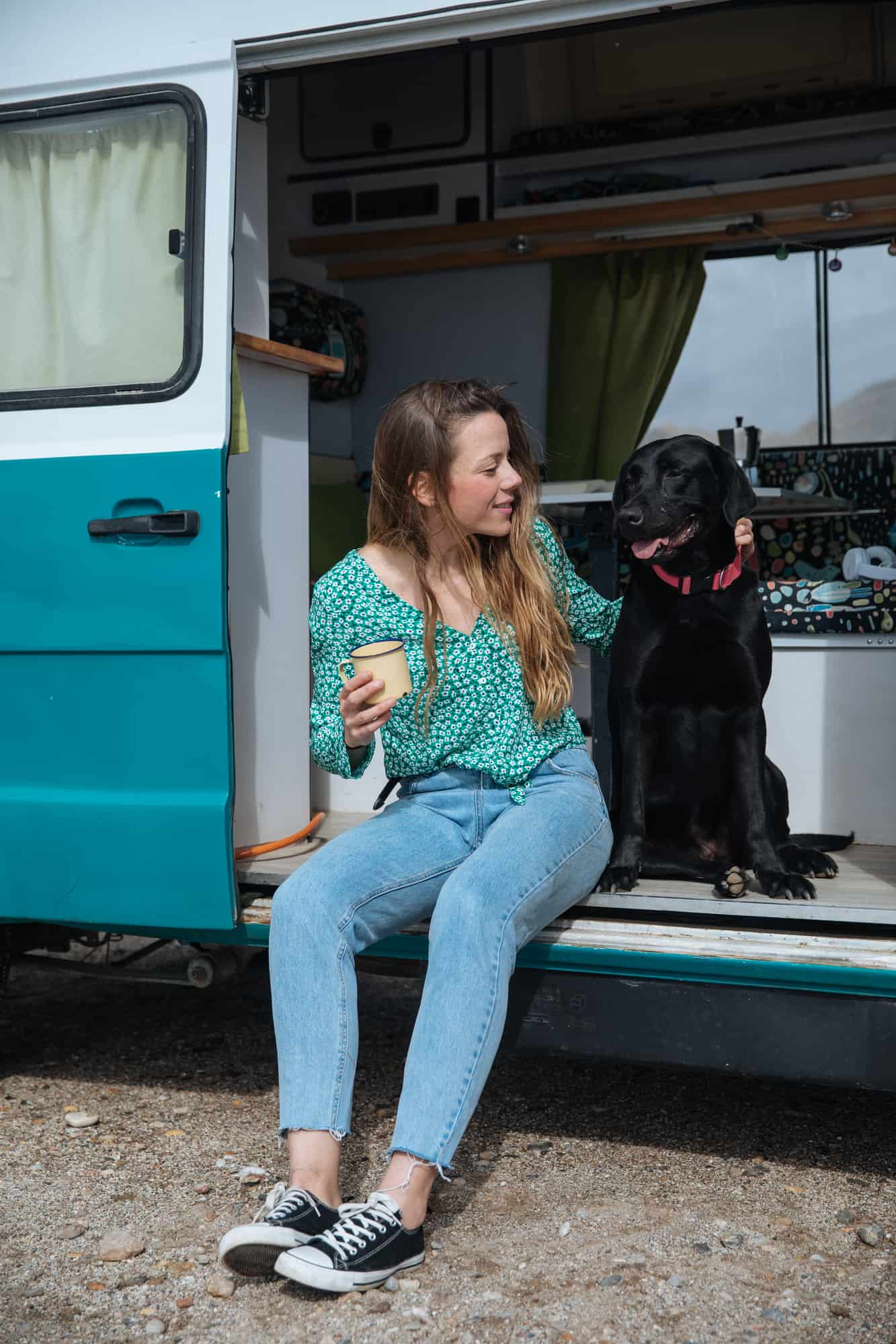 Happy young woman sitting with her black dog in the doorway of a camper van