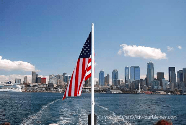 Flag on the back of a boat with the Seattle, WA skyline in the background