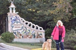 Visiting a pet-friendly museum is a great way to make the most of your vacation. (woman and golden retriever in front of ornate gate)