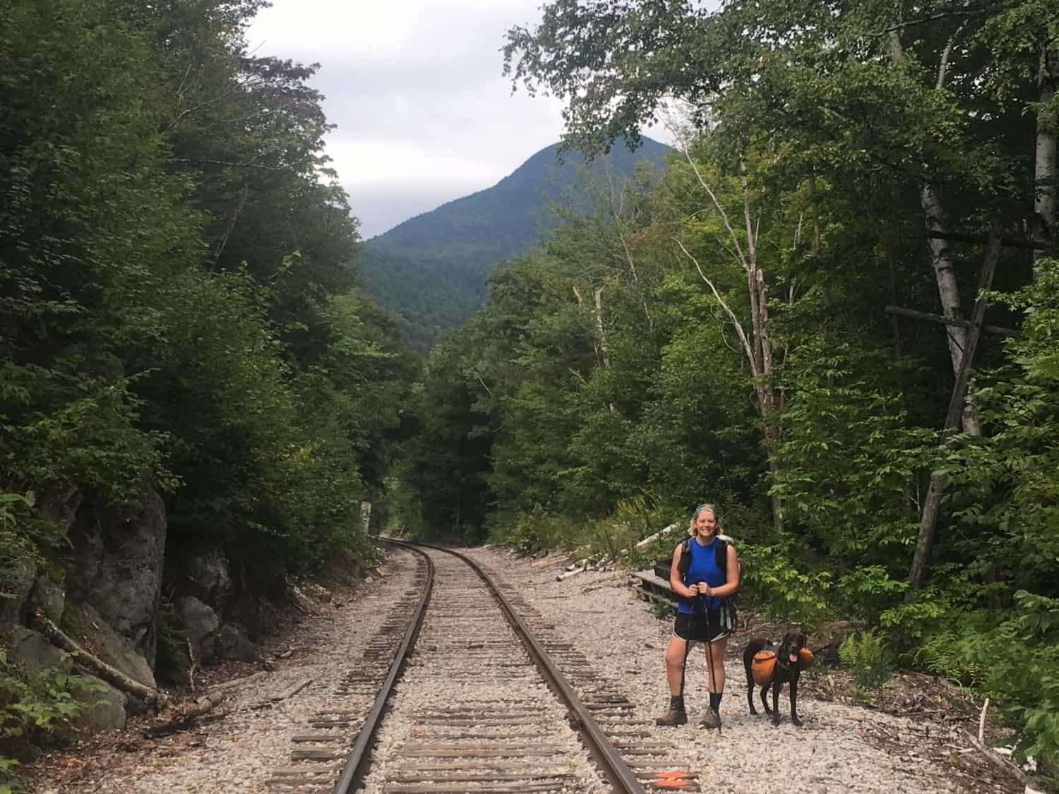 Dog and woman hiking along train tracks on the pet friendly Appalachian Trail in New Hampshire