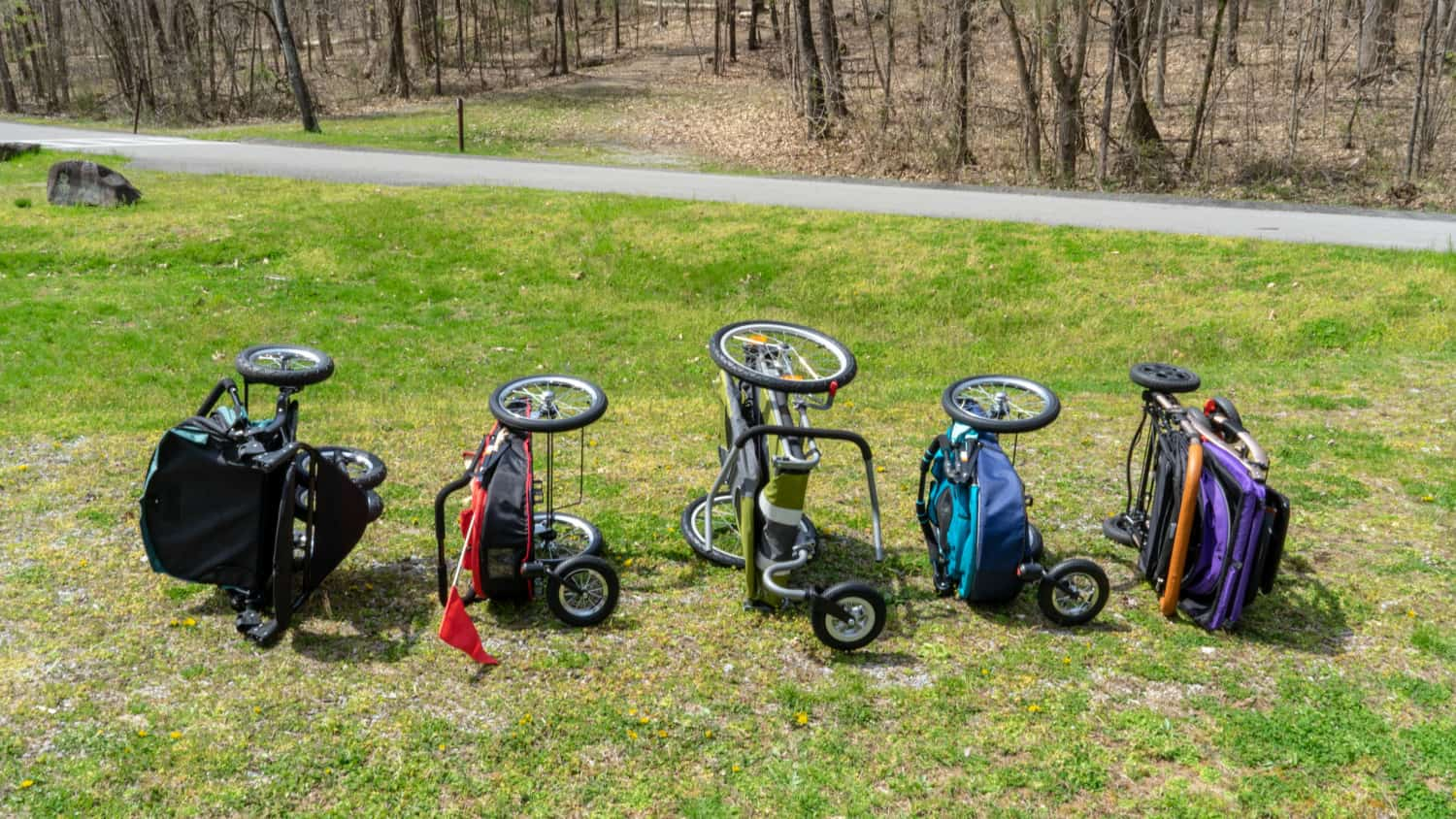 Five dog strollers in a folded position on their sides for comparison