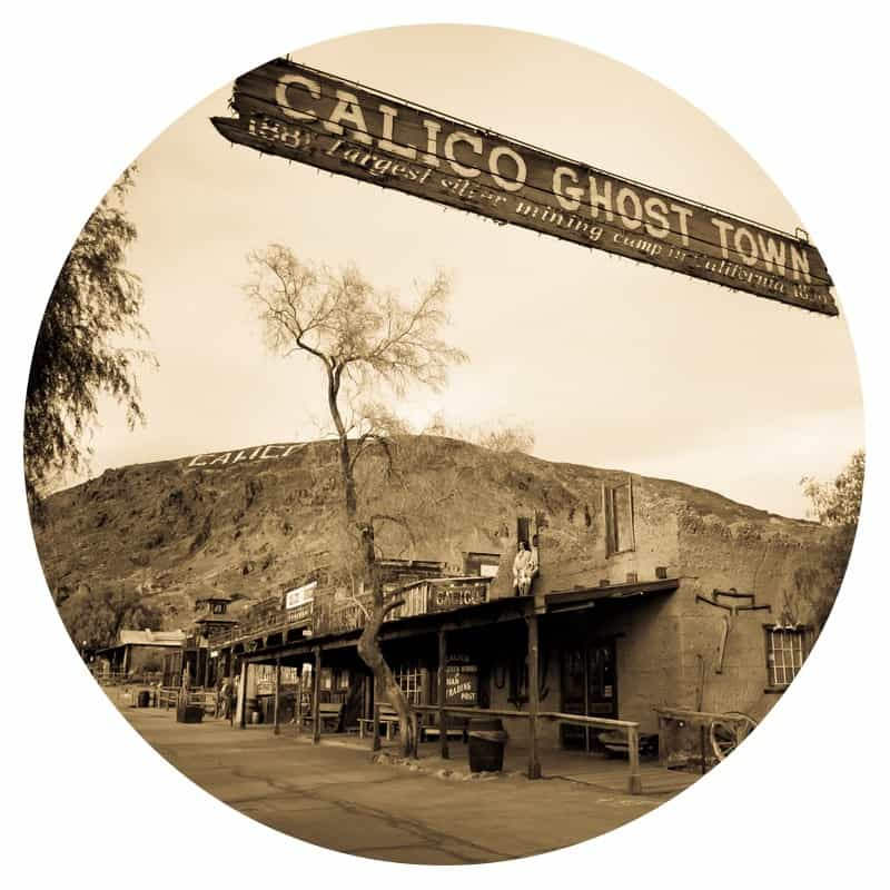 Black and white photo of a sign hanging over the street that says Calico Ghost Town. This is a pet friendly attraction along historic Route 66.