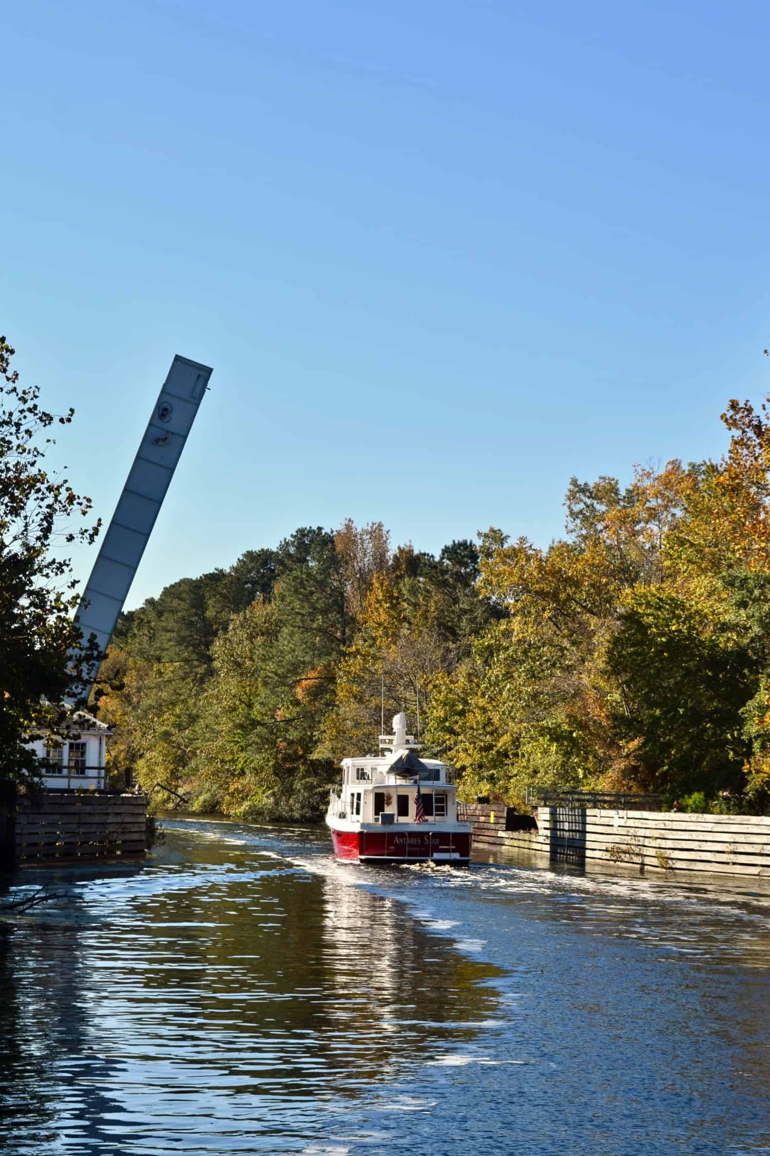 Red and white boat passing through the Bascule Bridge in the Great Dismal Swamp