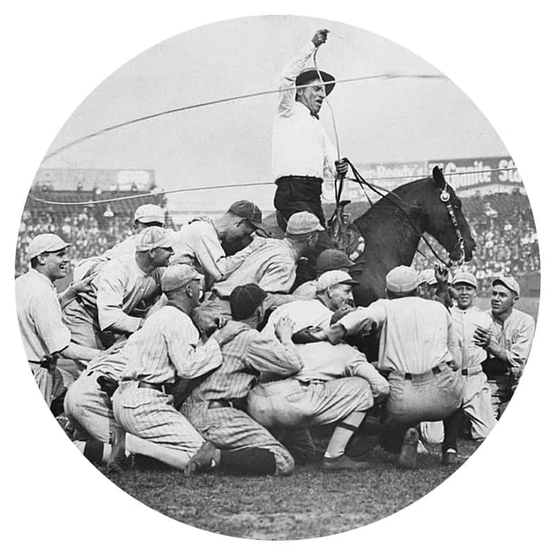 Black and white photo of Will Rogers horseback swinging a lasso around a baseball team
