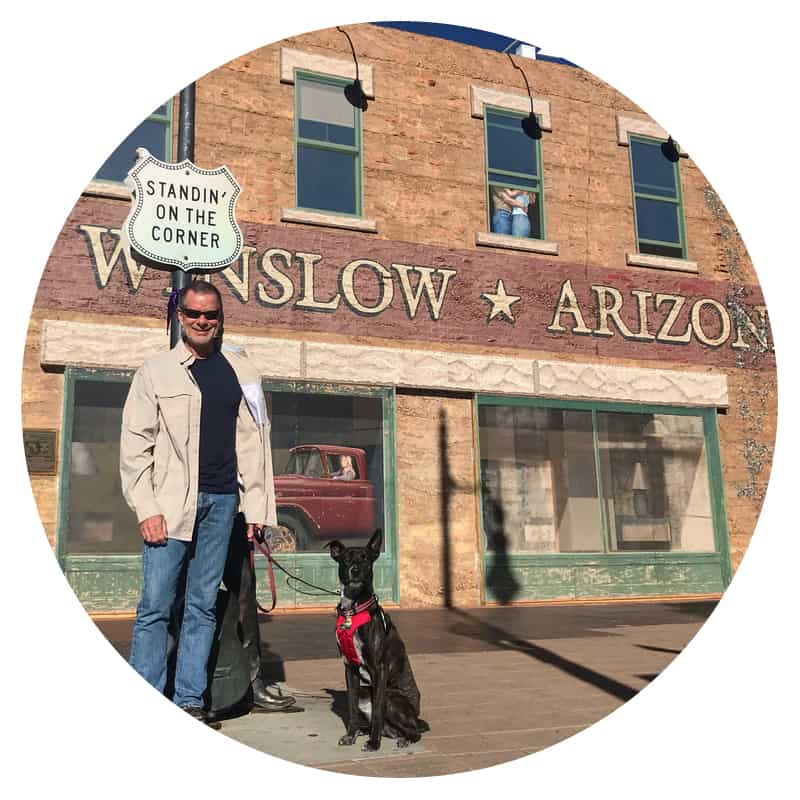 Man and a dog standing on the corner in Winslow, AZ