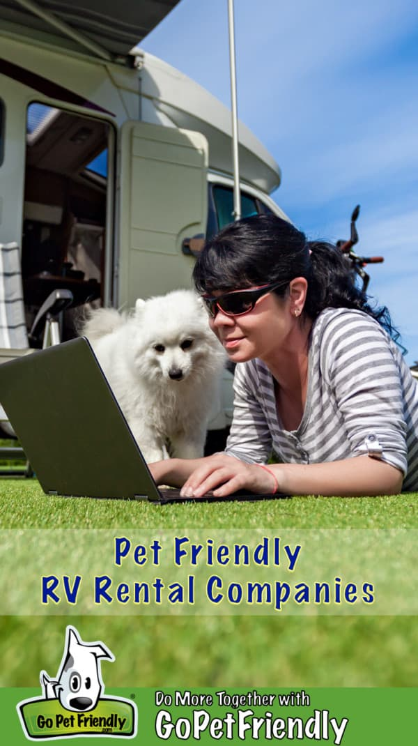 Woman laying in the grass with a dog in front of a pet friendly RV rental