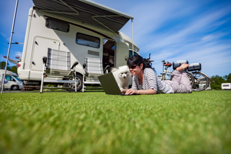 Woman lying on the grass with a dog looking at a laptop. Pet friendly RV rental in background