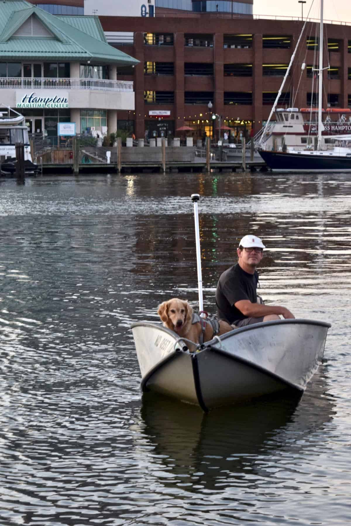 Golden retriever in dinghy with man.