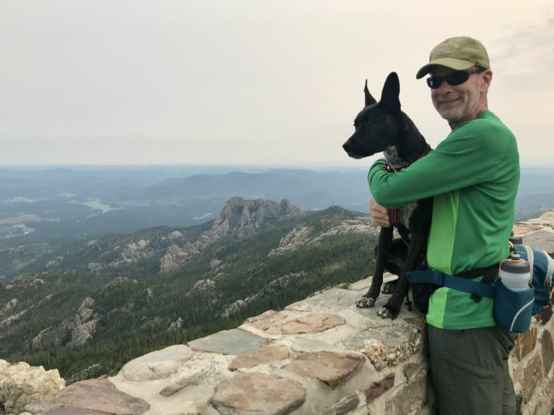 Man with a brindle dog at the fire tower on Black Elk Peak in the Black Hills, South Dakota
