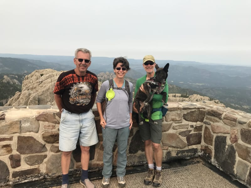Two men, a woman, and a dog at the fire tower on Black Elk Peak in the Black Hills, South Dakota