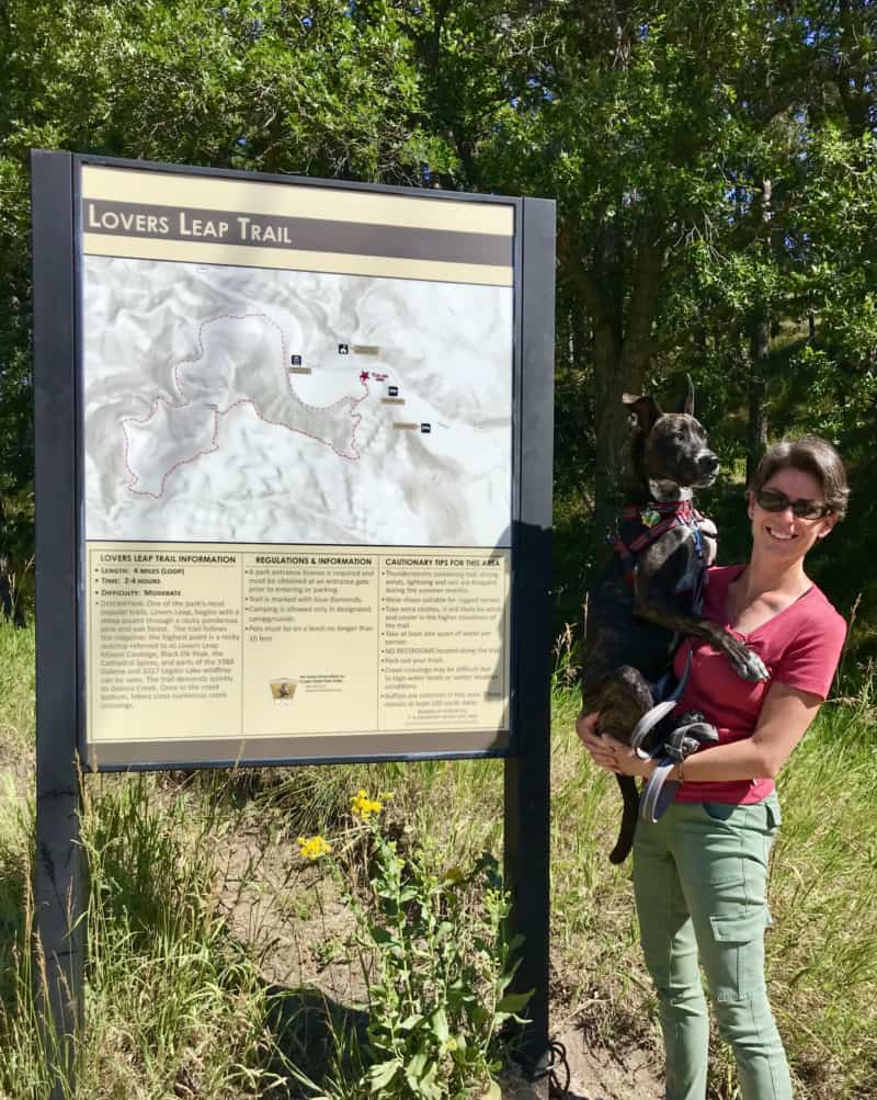 Woman holding a brindle dog beside the trailhead sign for Lover's Leap Trail in pet friendly Custer State Park, South Dakota