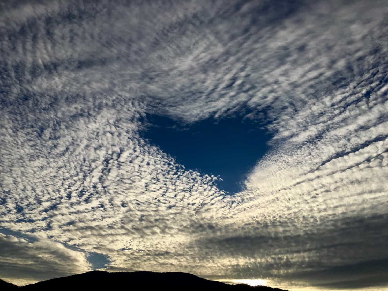 Heart-shaped hole in a cloudy sky