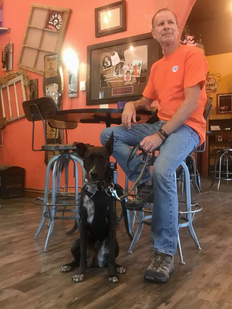 Brindle dog and man at pet friendly Naked Winery Tasting Room & Sick-N-Twisted Brew Pub in Hill City, SD