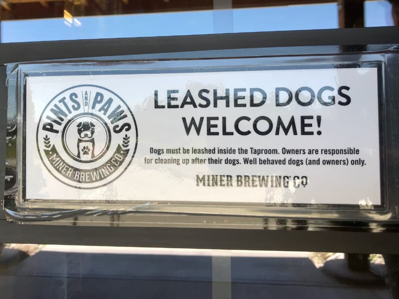 Leashed dogs welcome sign at pet friendly Miner Brewing Company in Hill City, SD