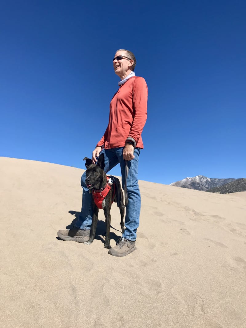 Man standing on a dune with a dog between his legs in Great Sand Dunes National Park