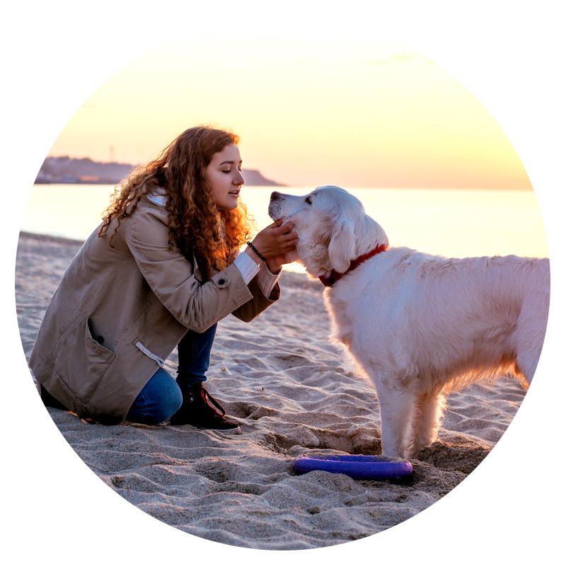 Woman in a jacket and a Golden Retriever dog on the beach in Virginia Beach, VA