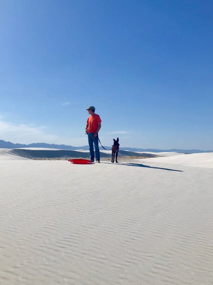 Man and dog with red sled in pet friendly White Sands National Park, NM