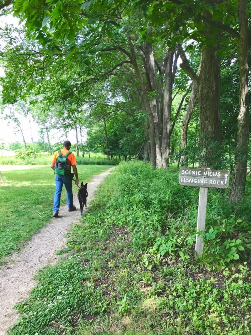 Man walking dog on trail at Effigy Mounds National Monument in Iowa
