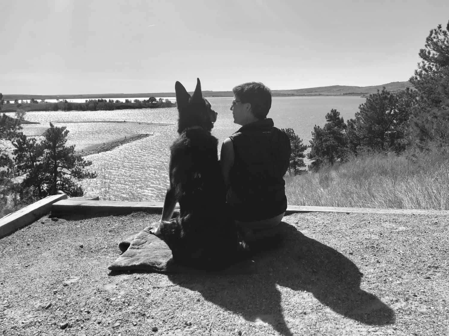 Black and white photo of a German Shepherd Dog and a woman smiling at each other overlooking a lake