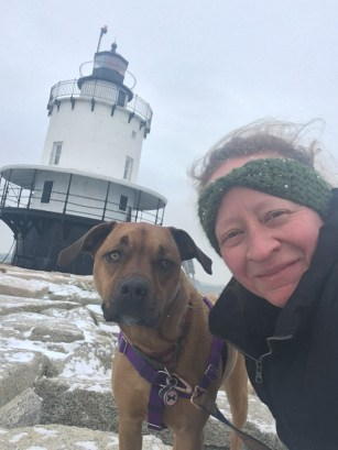 Woman and dog at a pet friendly lighthouse in New England