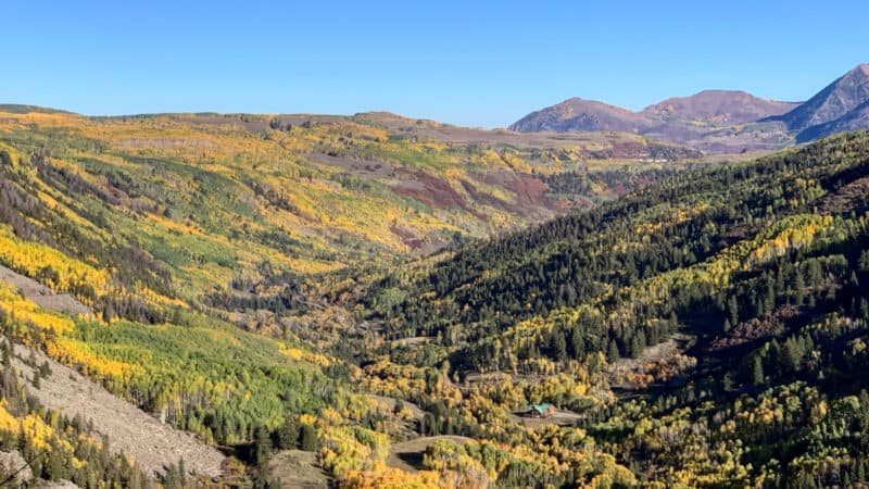 Mountain landscape with golden aspen trees and evergreens