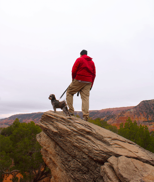 Man in red coat with a dog on a pet friendly trail overlooking a canyon