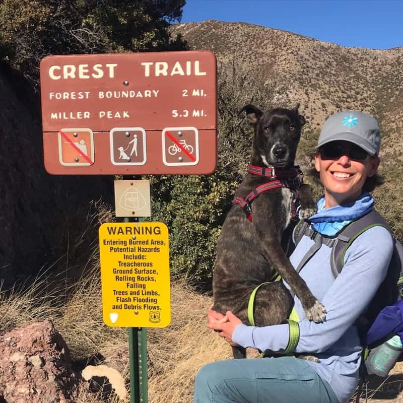 Woman holding dog beside sign for dog friendly Crest Trail at Coronado National Monument near Tucson, AZ