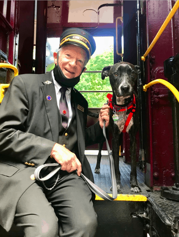 Happy train conductor sitting next to a brindle colored dog in a red harness on the Leigh Gorge Scenic Railway in Jim Thorpe, PA