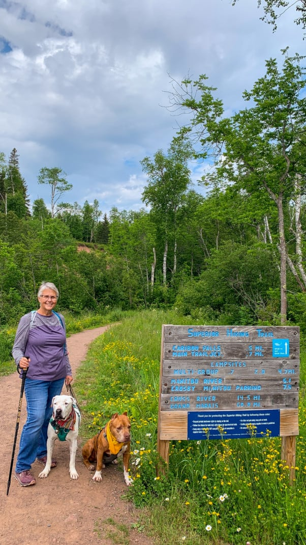 A woman, a white dog, and a brown dog standing at the start of a hiking trail next to the trail sign at Caribou Falls State Wayside on the North Shore in Minnesota.