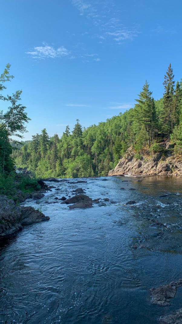 View of a river at the top of a waterfall with pines trees in the background at Tettegouche State Park on the North Shore in Minnesota