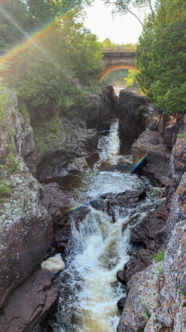 A river rushes through a gorge with bridge and trees in the background at Temperance River State Park on the North Shore in Minnesota