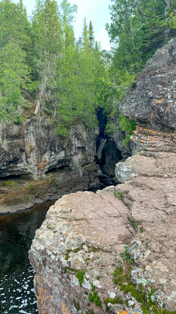 A waterfall can barely bee seen through the opening of a pine tree speckled gorge at Temperance River State Park on the North Shore in Minnesota.