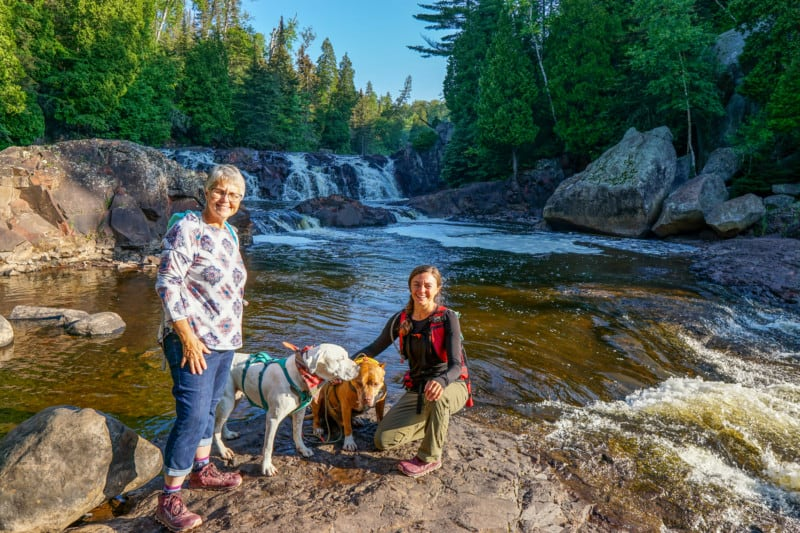 Two women and two dogs in front of a waterfall with trees in the background at Tettegouche State Park in Minnesota
