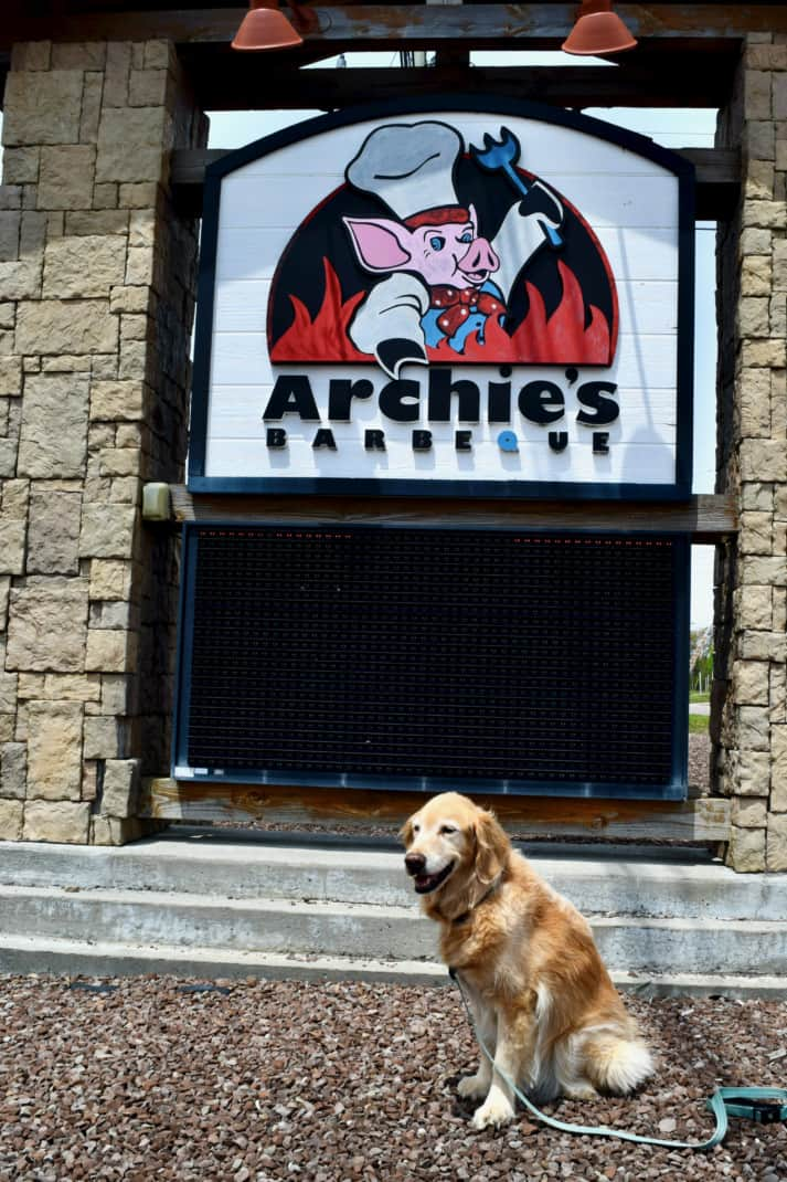 Golden Retriever sitting in front of an Archies BBQ sign