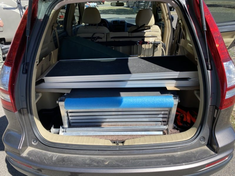Collapsible steps, deck, and dog ramp folded up in the storage area of a Honda CRV