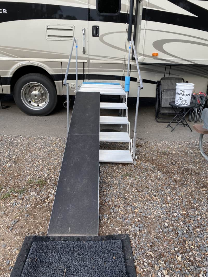 Folding deck and stairs with a dog ramp set up against a motorhome