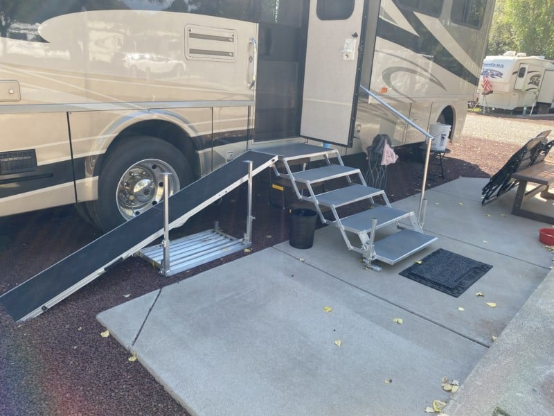 Folding stairs with a dog ramp set up against a motorhome